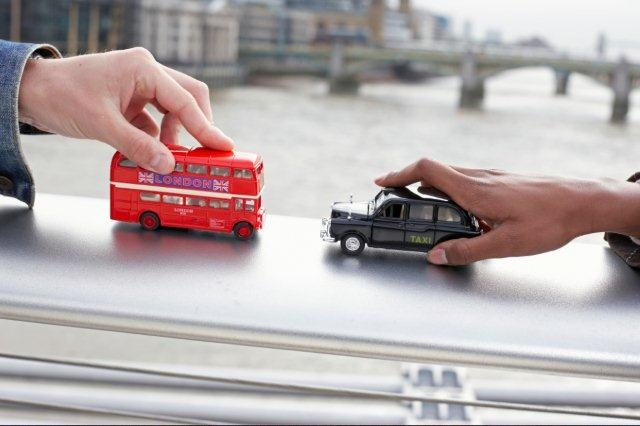 hands-playing-with-london-bus-and-taxi-toys